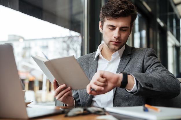 Концентрированный бизнесмен сидит за столом в кафе с ноутбуком, держа книгу и глядя на наручные часы