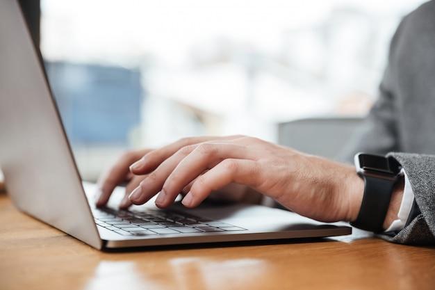 カフェのテーブルに座ってラップトップコンピューターを使用して実業家の画像をトリミング