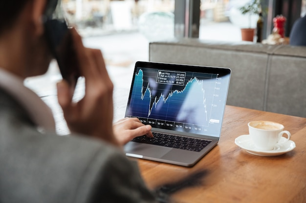カフェのテーブルに座って、スマートフォンで話しながらノートパソコンのインジケーターを分析する実業家の画像をトリミング