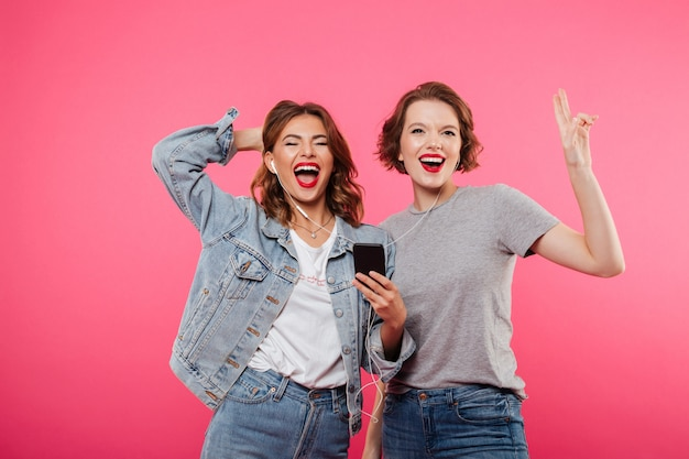 Счастливые друзья женщин с помощью мобильного телефона прослушивания музыки