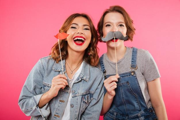 Смешные женщины друзья, держа поддельные губы и усы.