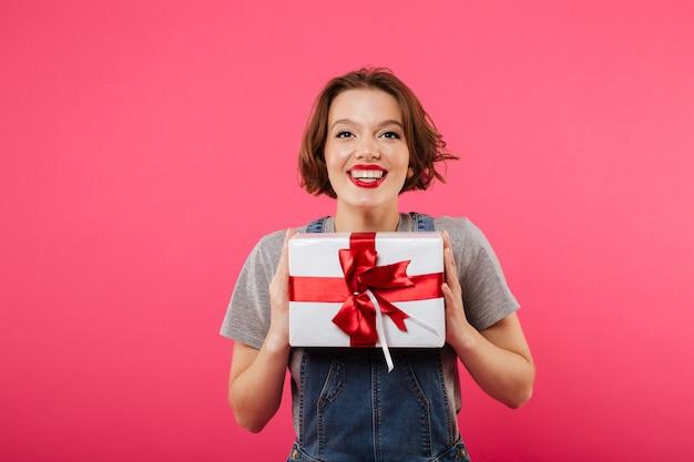 ギフト用の箱を保持している感情的な若い女性。