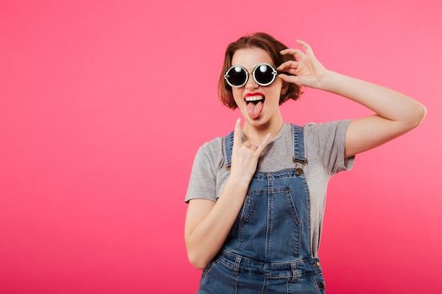 Веселая молодая женщина, показывая язык и рок жест.
