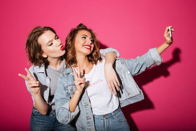 Веселые две женщины делают селфи по телефону