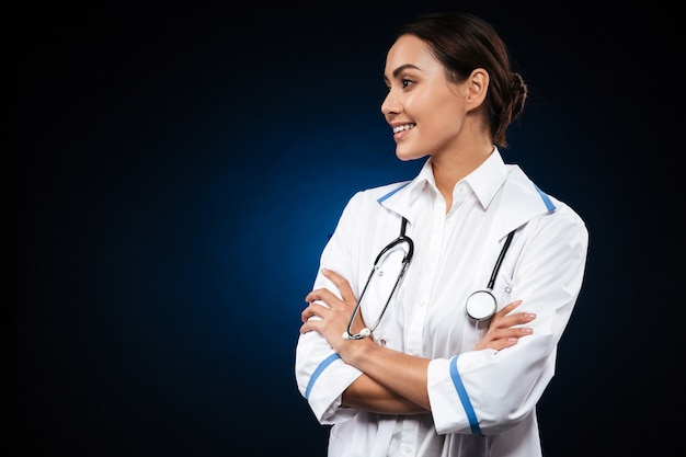 Довольно брюнетка женщина-врач смотрит в сторону и улыбается
