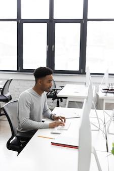 Молодой африканский офисный работник, сидя за столом