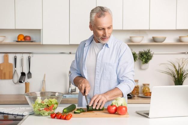 Красивый мужчина стоял на кухне с помощью ноутбука и приготовления пищи