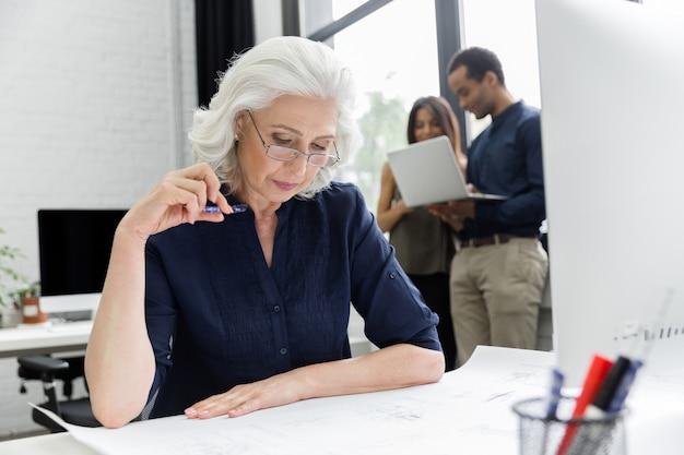 彼女の職場に座ってドキュメントを扱う成熟した実業家