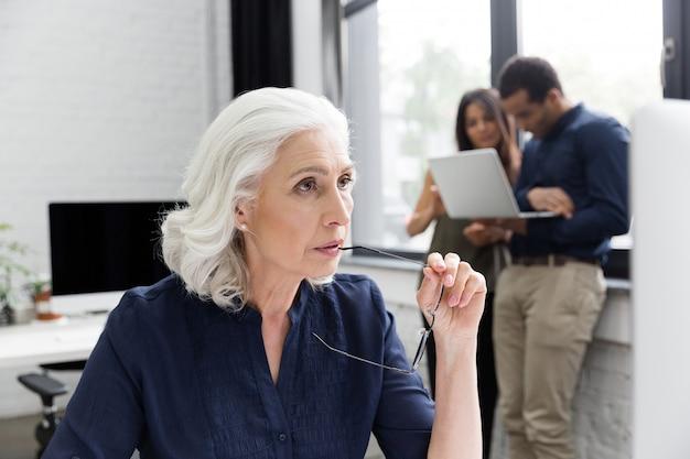 彼女の職場で働く物思いにふけるビジネス女性