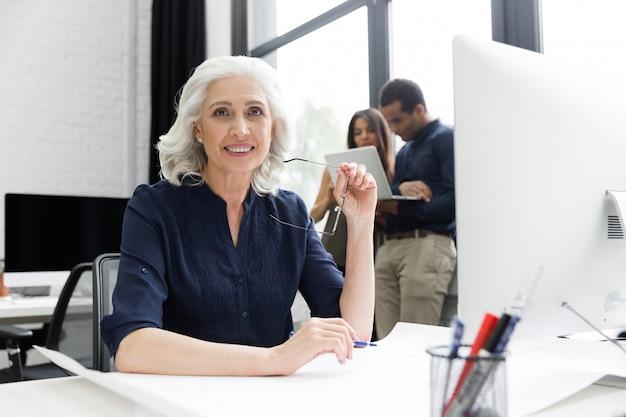 Улыбающаяся зрелая деловая женщина сидит на своем рабочем месте