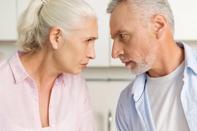 成熟した深刻な女性の近くに立っている怒っている成熟した男