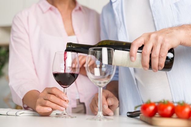 Обрезанное изображение зрелой любящей пары семьи пить вино