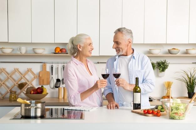成熟した幸せな愛情のあるカップルがワインを飲んでキッチンに立っています。