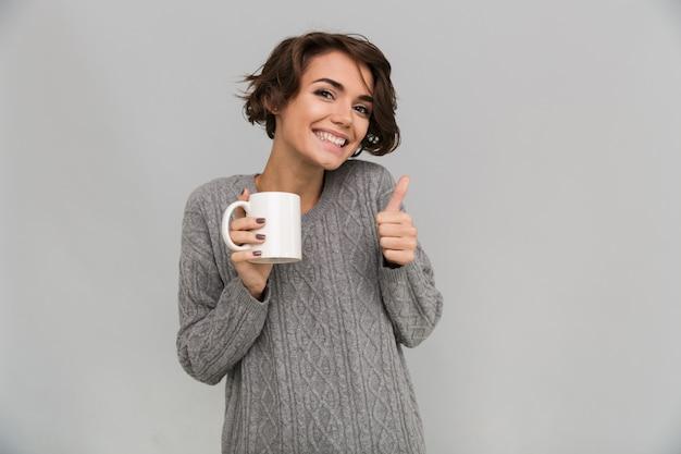 Чай счастливой молодой дамы выпивая показывая большие пальцы руки вверх показывать.