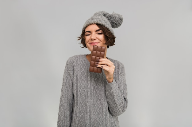 セーターとチョコレートを保持している暖かい帽子に身を包んだ女性。