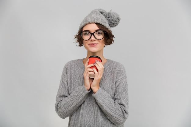 Счастливая женщина, одетая в свитер и теплую шапку, пить кофе.