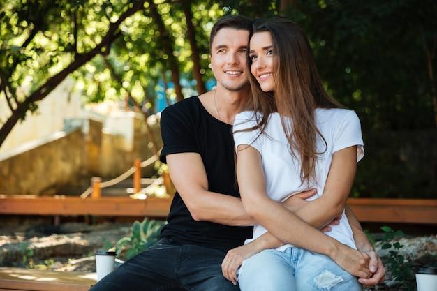 座っている愛の笑顔の魅力的なカップルの肖像画