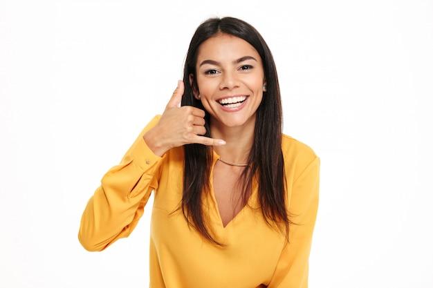 呼び出しジェスチャーを示す黄色のシャツで驚くほど幸せな若い女性。