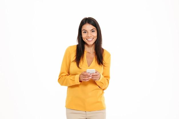 Портрет веселый молодой женщины, держащей мобильный телефон