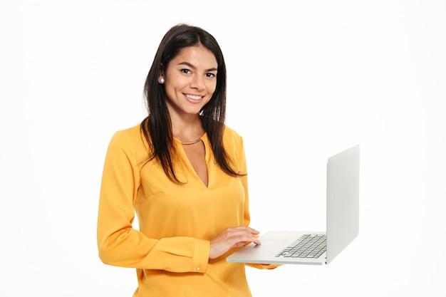 ラップトップコンピューターを保持している幸せなきれいな女性の肖像画