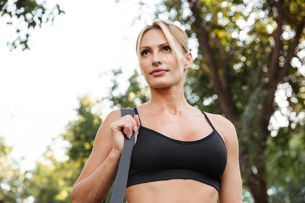バッグと立っているかなり強い若いスポーツ女性。