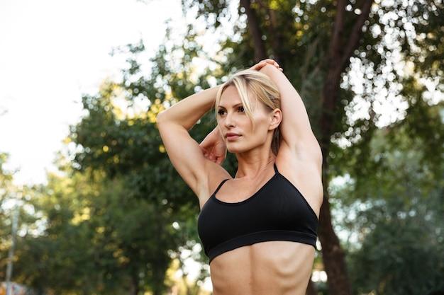 驚くほど強い若いスポーツ女性はスポーツの練習をする