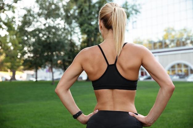驚くほど強い若いスポーツ女性の背面図