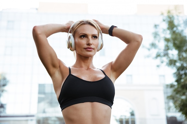 音楽を聴く強い若いスポーツ女性を集中