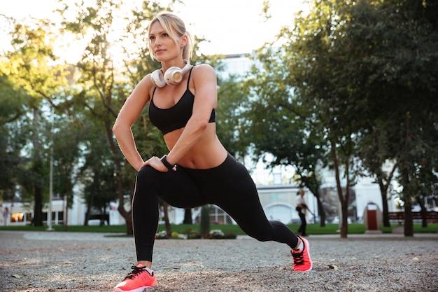 美しい強い若いスポーツ女性はスポーツ演習を行う