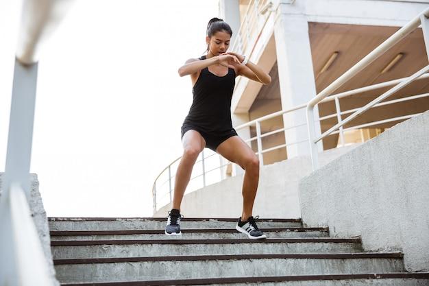 Портрет фитнес женщины делают спортивные упражнения