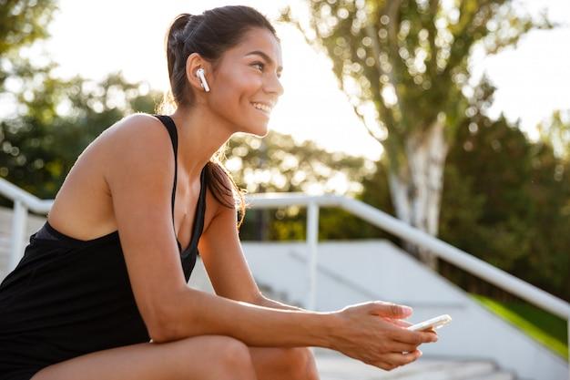 Портрет счастливой женщины фитнеса в наушниках