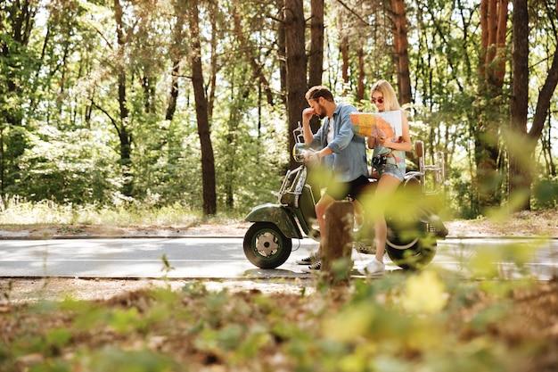 屋外スクーターの上に座ってマップを保持している疲れている愛情のあるカップル。
