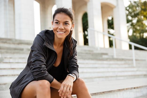 Портрет улыбающейся спортсменки в наушниках