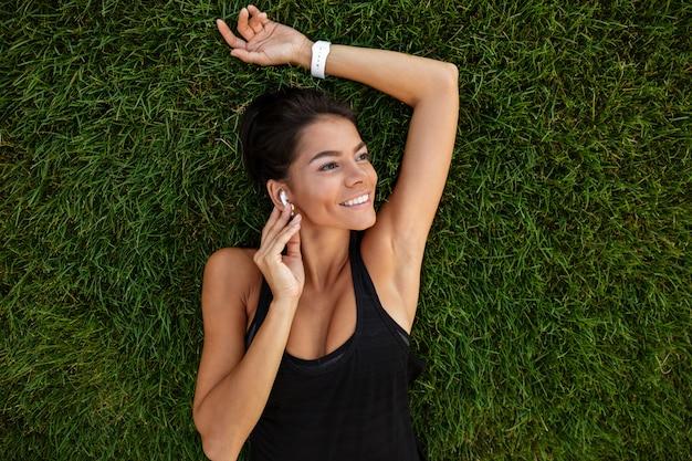 Взгляд сверху счастливой женщины фитнеса в класть наушников