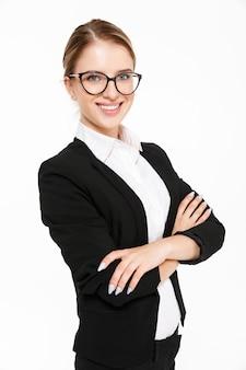 Вертикальное изображение улыбается блондинка деловая женщина в очках, позирует в сторону со скрещенными руками на белом