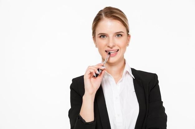 Улыбающаяся блондинка деловая женщина кусает ручку и над белой стеной