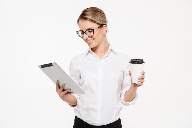 Улыбаясь блондинка бизнес-леди в очках с помощью планшетного компьютера, держа чашку чая на белой стене