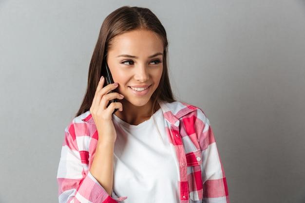 笑顔の若い女性、携帯電話で話している、よそ見のクローズアップショット