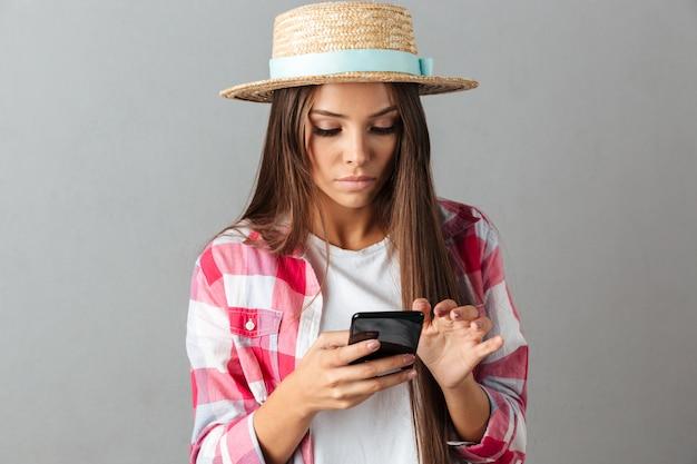 携帯電話を見て麦わら帽子で深刻な若い女性のクローズアップ写真