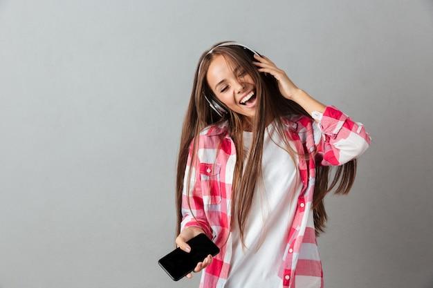 Довольно молодая женщина в наушниках слушает музыку и петь с закрытыми глазами