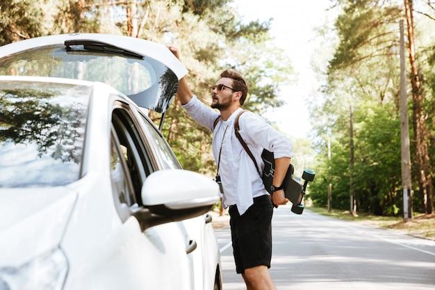 Человек со скейтбордом на улице стоит возле автомобиля