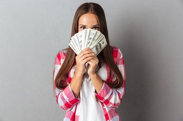 Симпатичная брюнетка держит бумажные деньги в руках и смотрит из них