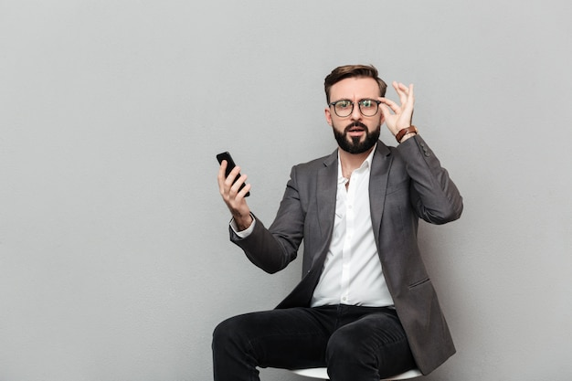 灰色の分離された椅子に座って、携帯電話を使用してカメラを探している眼鏡の深刻な男の水平の肖像
