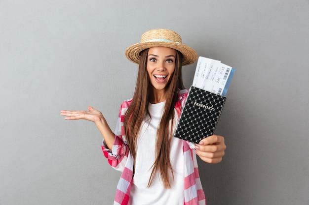 飛行機のチケットでパスポートを示す麦わら帽子で笑顔の幸せな女性旅行者の肖像画間近します。