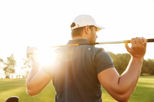 ゴルフクラブを運ぶ若い男の背面図