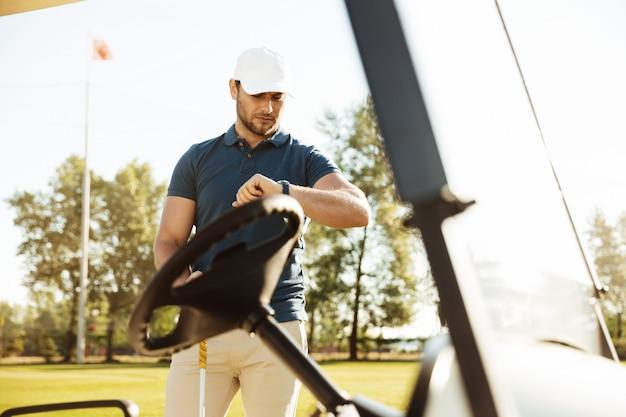 腕時計を見て若い男性ゴルファー
