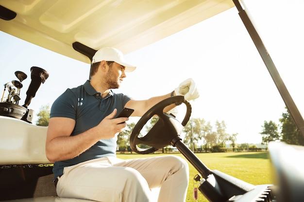 若いスポーツマン運転ゴルフカート