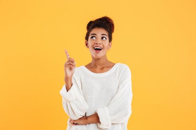 Счастливая афроамериканская леди, указывающая с пальцем, чтобы скопировать пространство