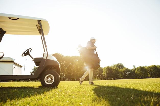 男性のゴルファーがゴルフバッグで歩く