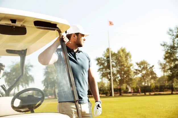 Молодой мужчина гольфист стоя